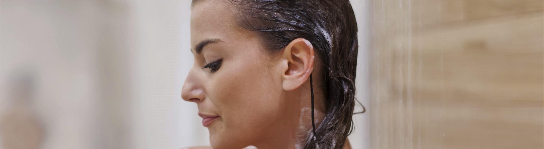 Femme en train de se laver ses cheveux avec un shampoing pour cheveux colorés